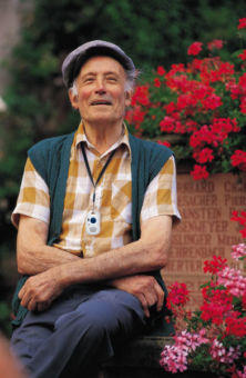 man sitting in front of flowers while wearing pendant with button